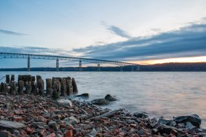 A photo of the Kingston-Rhinecliff Bridge and the wood pilings along the shores of the Hudson River at Charles Rider Park at sunrise on a January morning.