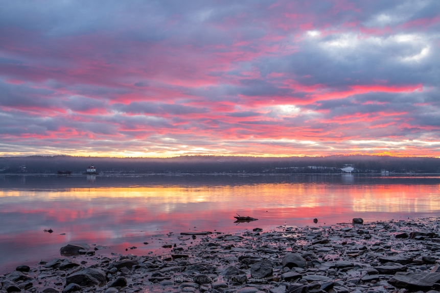 Pink, magenta, and orange clouds reflected on the Hudson River along the shores of the Esopus Meadows Preserve on a January morning.