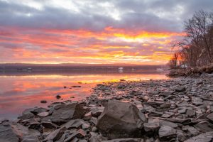 Orange clouds reflected on the Hudson River at Esopus Meadows Preserve during a January sunrise.