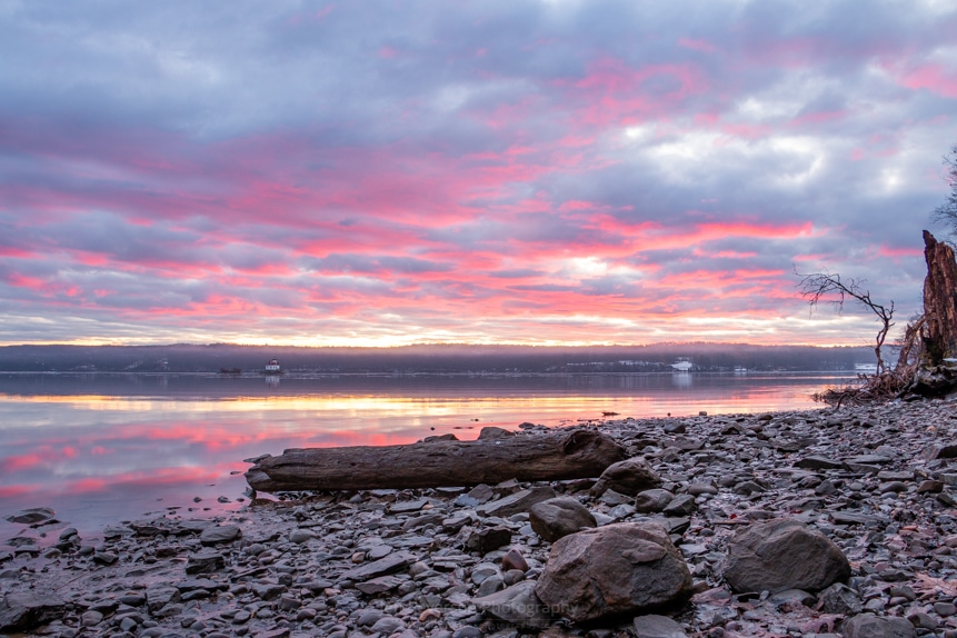 A photo of rocks and a log on the shoreline of the Hudson River during a January sunrise.