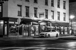 A black and white photo of a car parked in front of an Italian restaurant in the Rondout Historic District.
