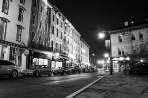 A black and white photo of West Strand Street at night.