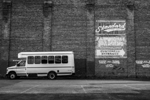 A black and white photo of a parking lot with old signage painted on a brick building with a bus parked in front of it.