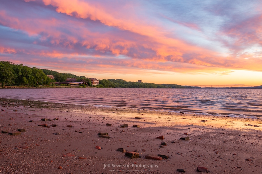 A photo of sunrise over the Hudson River along the brick-strewn beach at Kingston Point.