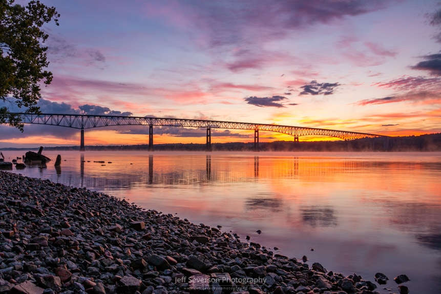 A photo of sunrise breaking over the Kingston-Rhinecliff Bridge from along the Hudson River at Charles Rider Park in Kingston, NY.
