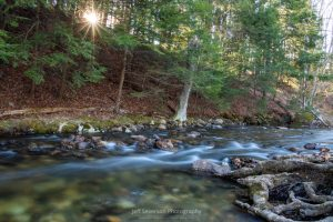 A long exposure of water running on the Coxing Kill at Mohonk Preserve as the sun rises above the ridge.