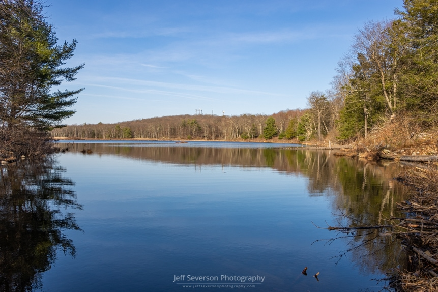 A landscape photo of Louisa Pond and surrounding tress reflected in it during an evening hike in March at Shaupeneak Ridge in Esopus, NY.