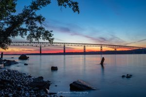 A photo of the first stages of a June sunrise appearing behind the Kingston-Rhinecliff Bridge as seen from the shores of the Hudson River at Charles Rider Park.