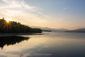A photo of the sun setting behind the treeline with Ashokan Reservoir in the foreground and the Catskill Mountains in the background.