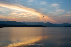A photo of clouds reflected in the Ashokan Reservoir at sunset in August with the Catskill Mountains silhouetted in the background.