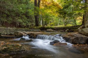 A photo of a small waterfall on the Coxing Kill at Mohonk Preserve on an autumn morning.